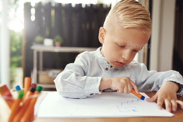 Handsome young boy drawing with crayons - Stock Photo - Images