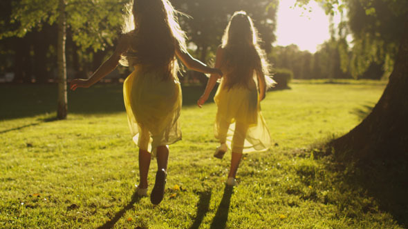 Two Girls are Running Away in Sunlight at Park