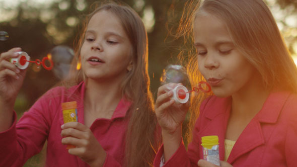 Two Twin Girls are Playing with Soap Bubbles