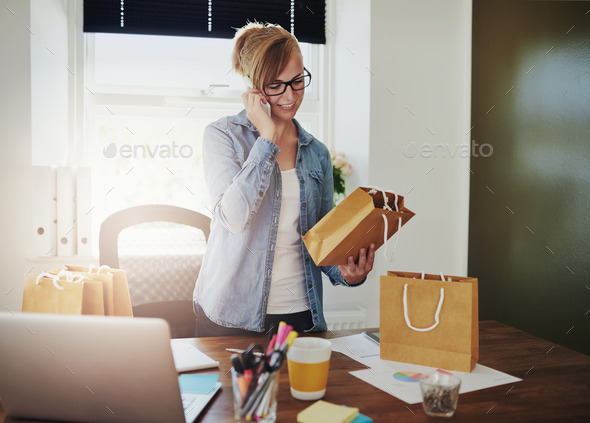 Motivated businesswoman placing orders on a phone - Stock Photo - Images