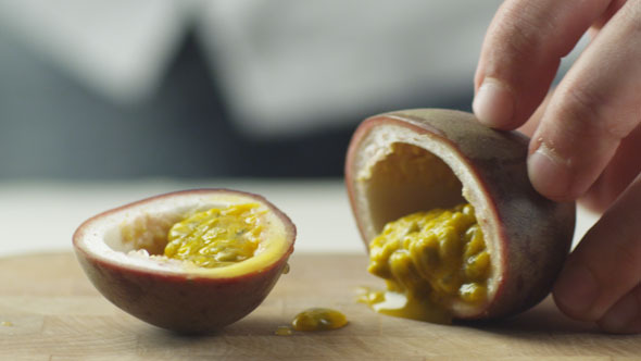 Cook is Slicing Passion Fruit with Knife