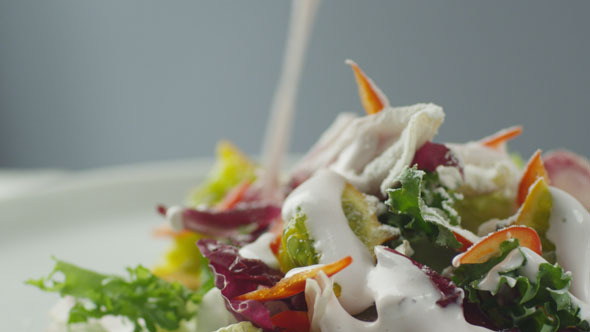 Cook Garnishing Vegetable Salad with Sour Cream