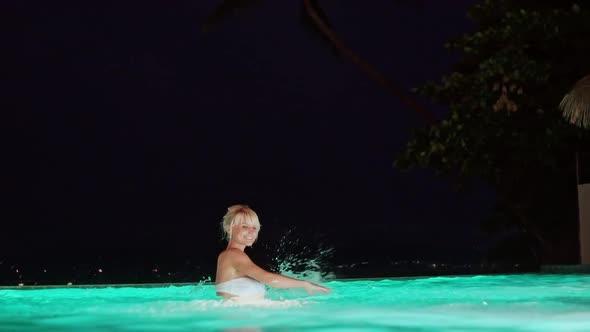 Beautiful Blond Woman Splashing in a Pool at Night