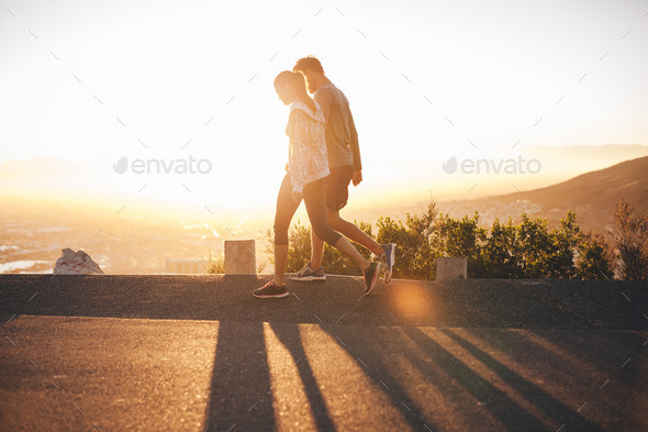 Couple walk along road at sunrise - Stock Photo - Images