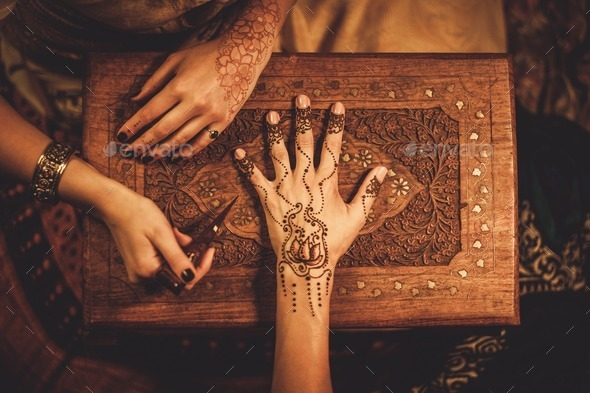 Drawing process of henna menhdi ornament on woman's hand - Stock Photo - Images