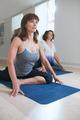 Women at yoga class practicing pigeon pose