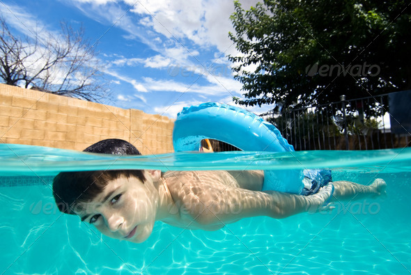 Boy swimming in pool with float ring - Stock Photo - Images