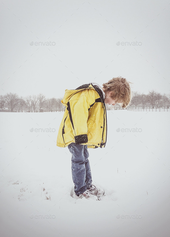 Boy Looking at Feet in the Snow - Stock Photo - Images