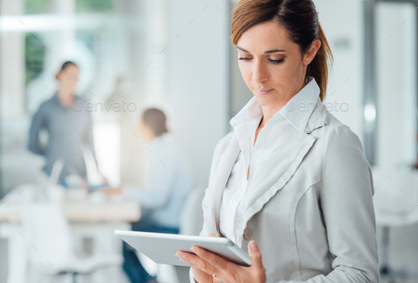 Professional business woman using a digital tablet - Stock Photo - Images