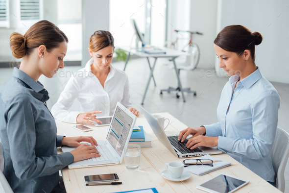 Confident women entrepreneurs working at desk - Stock Photo - Images