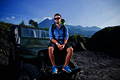 Handsome young caucasian man sitting on hood of a jeep, mountain