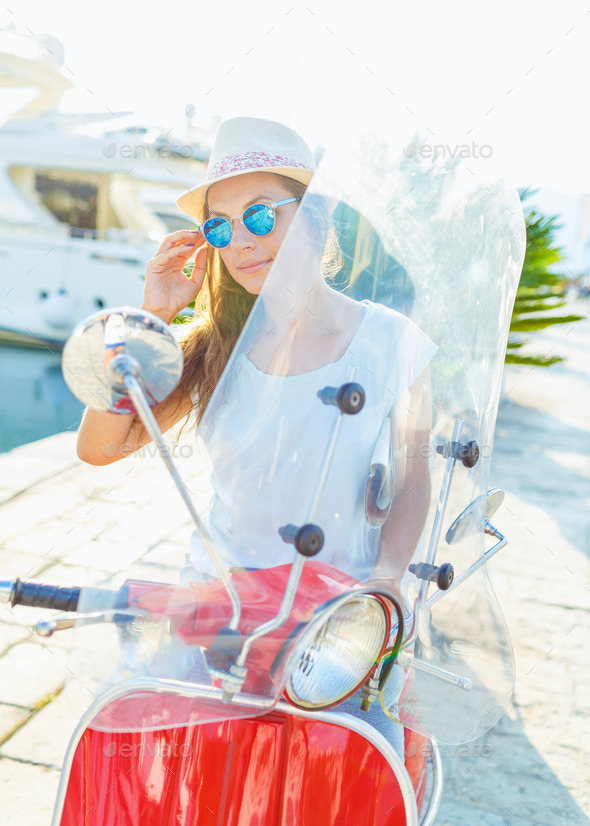 Young cheerful girl driving scooter  in the morning - Stock Photo - Images