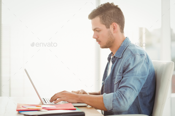 Side view of young man working on laptop while sitting at desk - Stock Photo - Images