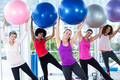 Portrait of smiling women holding exercise balls with arms raised in fitness studio