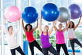 Women holding exercise balls with arms raised in fitness studio