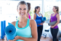 Portrait of cheerful woman holding exercise mat with friends at fitness studio - PhotoDune Item for Sale