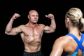 Bodybuilder flexing muscles in front of trainer against black bakground