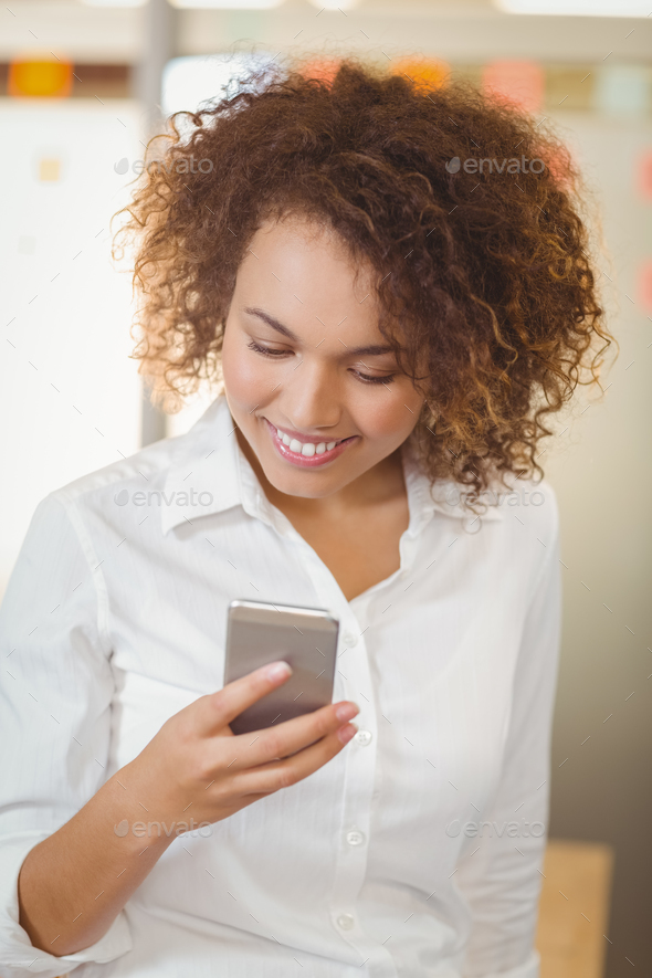 Smiling businesswoman using phone in office - Stock Photo - Images