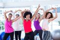Portrait of women exercising with arms raised in fitness studio
