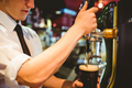 Cropped image of bartender holding beer glass below dispenser tap at bar counter - PhotoDune Item for Sale