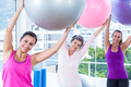 Portrait of happy women holding exercise balls with arms raised in fitness studio