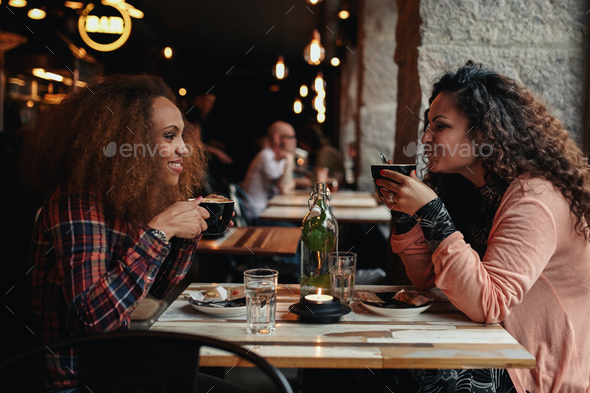 Two women talking and drinking coffee in a cafe - Stock Photo - Images