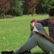 Man Reading While Sitting On The Grass - VideoHive Item for Sale