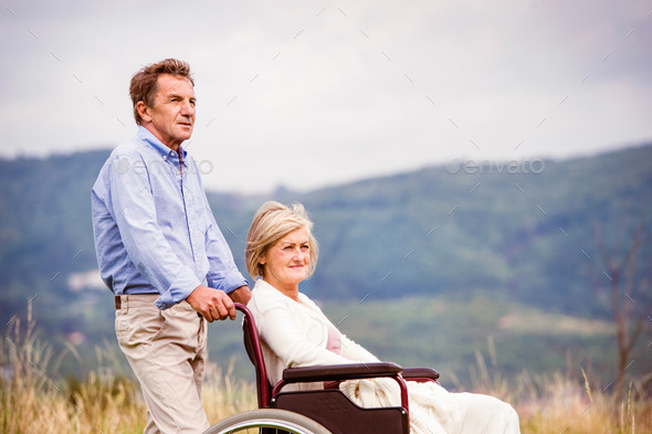 Man with woman in wheelchair - Stock Photo - Images