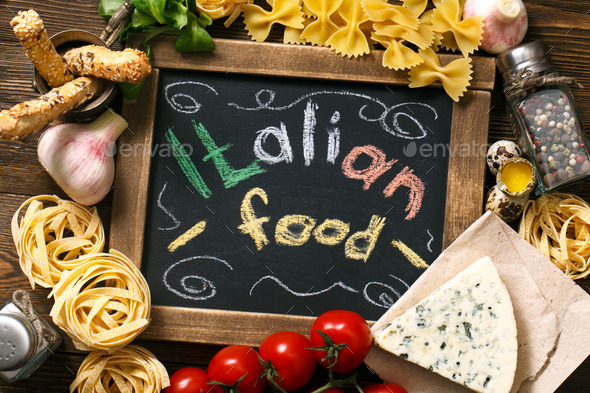 Italian food on vintage wood background with chalkboard - Stock Photo - Images