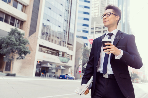 Businessman with coffee in a city - Stock Photo - Images