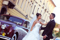 Beautiful bride and groom embracing near classic car