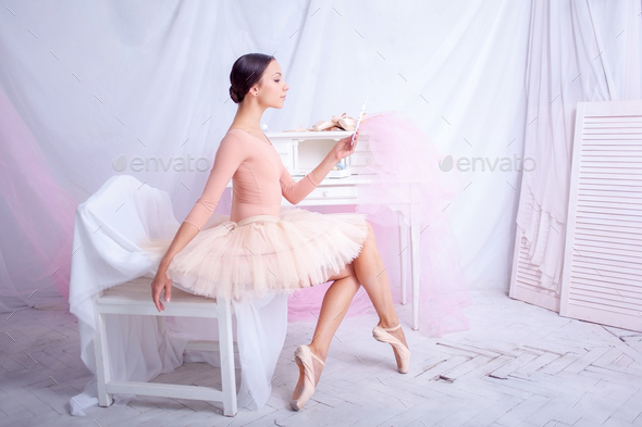 Professional ballet dancer looking in the mirror on pink - Stock Photo - Images