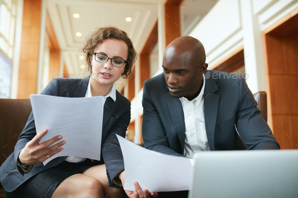 Two business partners sitting in cafe and discussing contract. - Stock Photo - Images