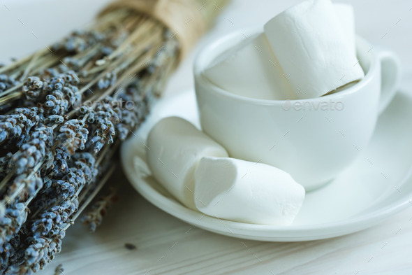 Marshmallow in a cup and lavender on a white wooden - Stock Photo - Images
