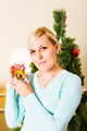 close up of woman hand holding christmas ball over living room and tree background