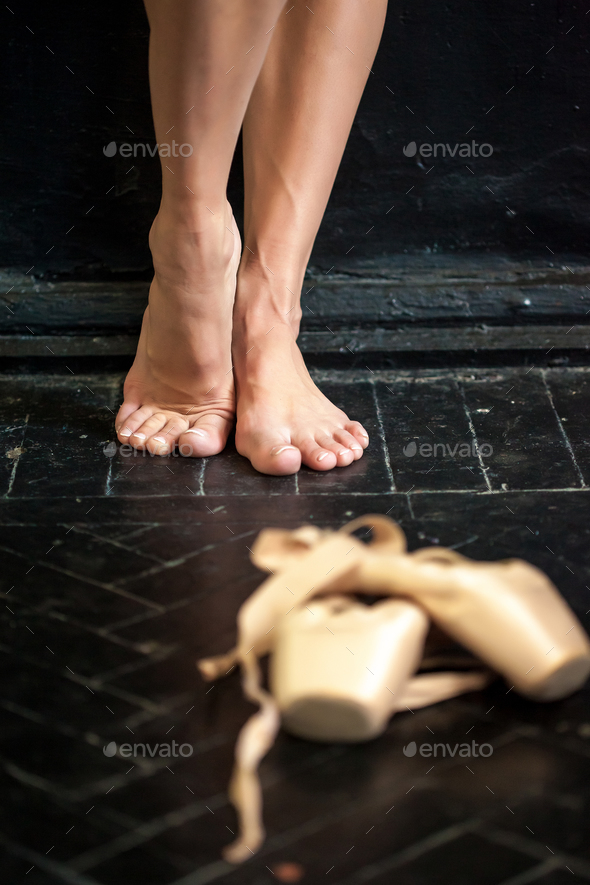 Close-up ballerina's legs and pointes on the black wooden floor - Stock Photo - Images