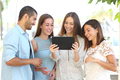 Group of four friends watching videos on a tablet - PhotoDune Item for Sale