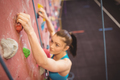 Woman climbing up rock wall at the gym