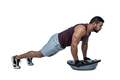 Muscular man doing bosu push ups against white background