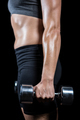 Muscular woman lifting heavy dumbbells on black background