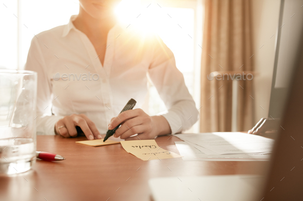 Woman writing on sticky notes at conference room - Stock Photo - Images