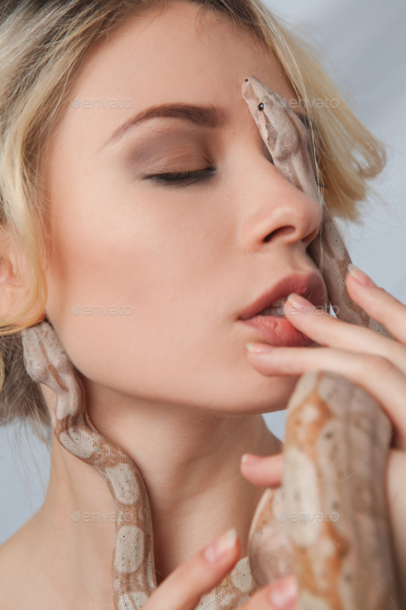Beautiful girl and the snake Boa constrictors, which wraps around her face - Stock Photo - Images