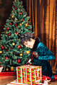 holidays and celebration  concept - woman opens gift box over christmas tree background.