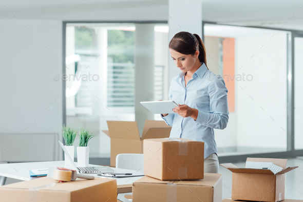 Business woman in her new office using a tablet - Stock Photo - Images