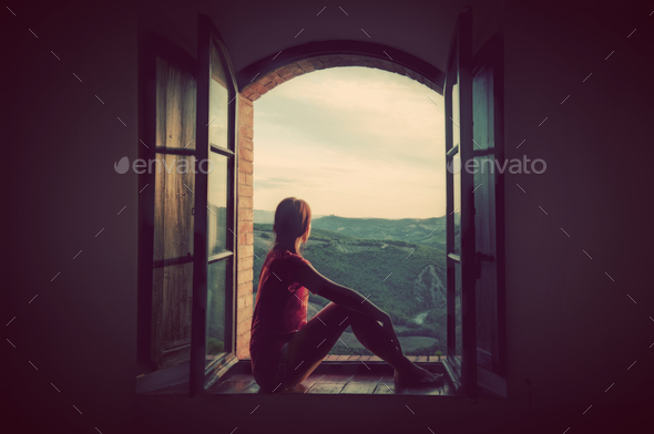 Young woman sitting in an open old window looking on the landscape of Tuscany, Italy. - Stock Photo - Images