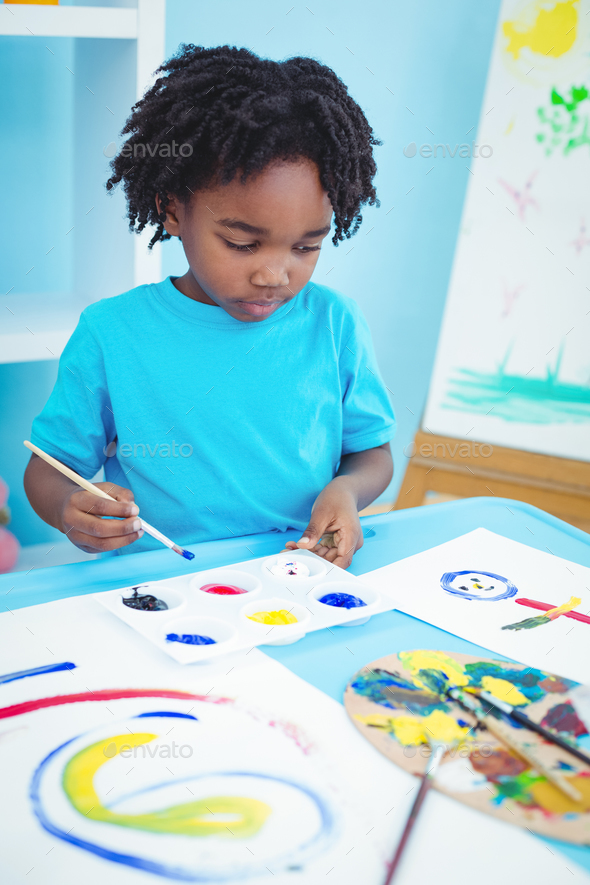 Happy kid enjoying arts and crafts painting at their desk - Stock Photo - Images