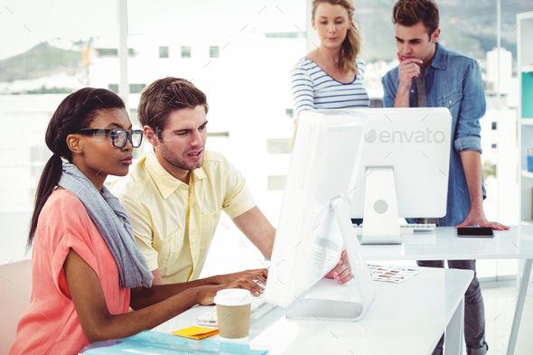 Creative business team working hard together on pc in casual office - Stock Photo - Images