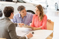Smiling couple buying a new car at new car showroom - PhotoDune Item for Sale