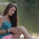 Girl Sitting On The River Bank With Phone Typing - VideoHive Item for Sale