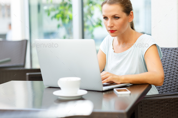 Young business woman sitting in a cafe with a laptop and coffee - Stock Photo - Images